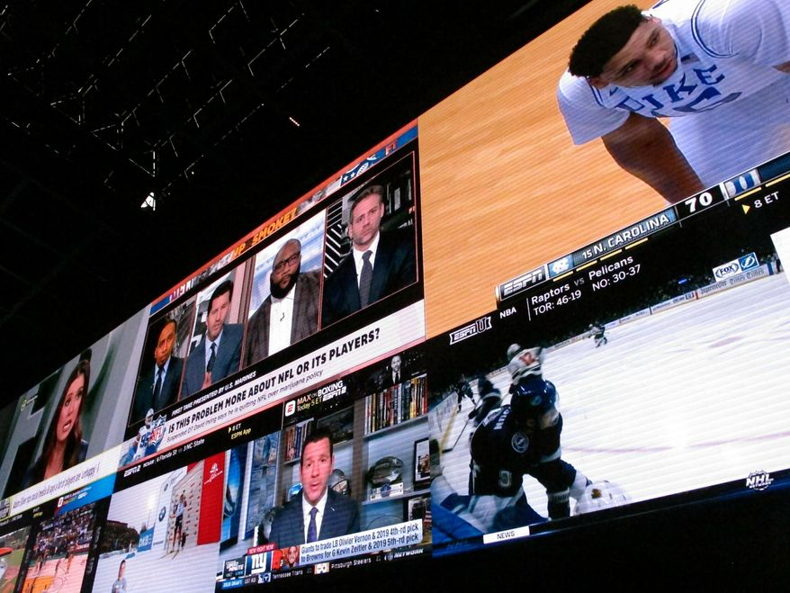 This March 8, 2019 photo shows giants video screens inside the sports betting lounge at the Tropicana casino in Atlantic City N.J. Figures released on March 13, 2019 show New Jersey gamblers have wagered almost $2 billion on sporting events since it started nine months ago. (AP Photo/Wayne Parry) **FILE**