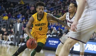North Dakota State's Vinnie Shahid (0) drives next to an Omaha player during an NCAA college basketball game for the Summit League men's tournament championship, Tuesday, March 12, 2019, in Sioux Falls, S.D. (Loren Townsley/Argus Leader via AP)