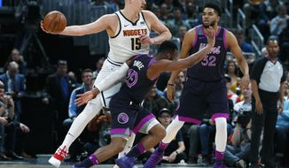 Denver Nuggets center Nikola Jokic, back left, looks to pass the ball as Minnesota Timberwolves guard Josh Okogie, left front, and center Karl-Anthony Towns defend in the first half of an NBA basketball game, Tuesday, March 12, 2019, in Denver. (AP Photo/David Zalubowski)