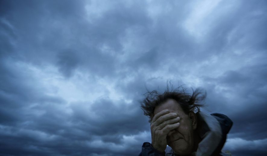 FILE - In this Friday, Sept. 14, 2018 file photo, Russ Lewis covers his eyes from a gust of wind and a blast of sand as Hurricane Florence approaches Myrtle Beach, S.C. According to a scientific report from the United Nations released on Wednesday, March 13, 2019, climate change, a global major extinction of animals and plants, a human population soaring toward 10 billion, degraded land, polluted air, and plastics, pesticides and hormone-changing chemicals in the water are making the planet an increasing unhealthy place for people. (AP Photo/David Goldman)