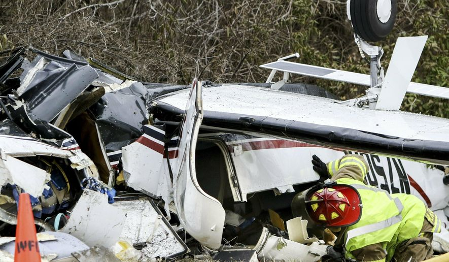 A firefighter checks the inside of a small single engine plane that crashed on Tuesday, March 12, 2019 at the intersection of Floraville Road and Gillmore Lake Road northeast of Waterloo, Ill. A single engine aircraft believed to have been carrying four passengers has crashed in southern Illinois. Authorities say the plane went down Tuesday northeast of Waterloo, in Monroe County. The identity and conditions of the passengers wasn't immediately known. (Colter Peterson/St. Louis Post-Dispatch via AP)