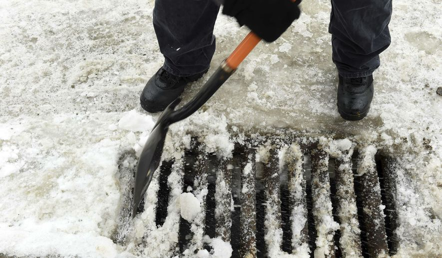 Maintenance supervisor Dan Leach frees storm drains of ice and snow at Episcopal Church Homes in St. Paul, Minn. on Tuesday, March 12, 2019. The rain that began falling Tuesday in the Twin Cities was expected to continue through Thursday, making for soggy, foggy -- and possibly icy -- conditions. A flood watch is in effect for the area Wednesday and Thursday, with temperatures forecast to reach into the 40's, triggering considerable snow melt, according to the National Weather Service.  (Scott Takushi/Pioneer Press via AP)
