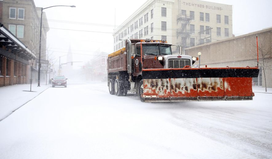 A snow plow rumbles north on Capitol Avenue during a blizzard on Wednesday, March 13, 2019, in Cheyenne, Wyo. White-out conditions closed I-80, I-25, and U.S. 85, effectively closing off the state capital from Nebraska, Colorado and the rest of Wyoming. (Jacob Byk/The Wyoming Tribune Eagle via AP)
