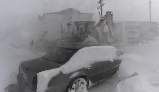 A man clears snow drifts with a bulldozer Thursday in Limon, Colorado. A sudden drop in barometric pressure crippled the area with heavy snow and high winds. (Associated Press)