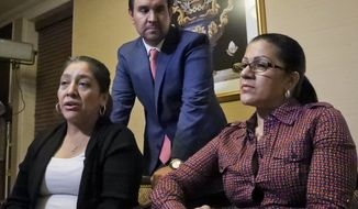 Attorney Anibal Romero, center, joins his clients Victorina Morales, left, and Sandra Diaz, right, during an interview, Friday Dec. 7, 2018, in New York. Morales and Diaz, who recalled their experience working at President Donald Trump's golf resort in Bedminster, N.J., say they used false legal documents to get hired and supervisors knew it. (AP Photo/Bebeto Matthews)