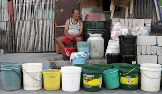 A man sits beside rows of pails as he waits for water trucks return to their area after several days without water in Mandaluyong, metropolitan Manila, Philippines on Thursday, March 14, 2019. Aside from the daily line of residents waiting for water rations from trucks, many businesses like laundry shops, carwash and water purifying stations in some parts of metropolitan Manila have been affected by a water shortage from the Manila Water Company due to low levels at the La Mesa dam and the onset of El Nino which causes below normal rainfall conditions. (AP Photo/Aaron Favila)