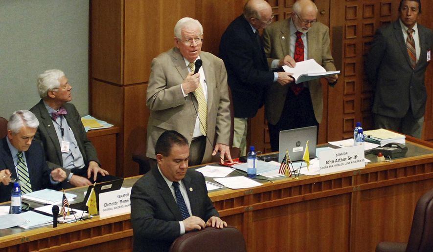 Democratic Sen. John Arthur Smith, of Deming, at rear with microphone, guides a $700 million annual spending increase from New Mexico's general fund through approval by the state Senate on Wednesday, March 13, 2019, in Santa Fe, N.M. The House and Senate are moving closer to agreement that would increase spending on public education by nearly half a billion dollars and channel a windfall in tax income toward infrastructure and economic stimulus. (AP Photo/Morgan Lee)