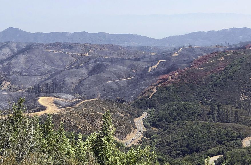 FILE - This Aug. 10, 2018, file photo, taken near Lakeport, Calif. shows dirt paths created by bulldozers in an effort to contain part of the largest wildfire on record in California. An environmentalist group is questioning the use of bulldozers to fight major wildfires, saying they're ineffective and leave lasting environmental damage. The Firefighters United for Safety, Ethics, & Ecology organization released a report Thursday, March 14, 2019, detailing bulldozers' use during a Northern California wildfire in July. (AP Photo/Jonathan J. Cooper, File)
