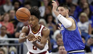 Cleveland Cavaliers' Collin Sexton, left, passes the ball around Orlando Magic's Nikola Vucevic during the first half of an NBA basketball game, Thursday, March 14, 2019, in Orlando, Fla. (AP Photo/John Raoux)