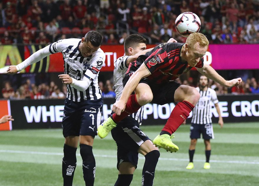 Atlanta United midfielder Jeff Larentowicz tries to head the ball into the net on a corner kick with Monterrey defender Johan Vasquez blocking the shot during the second half in a CONCACAF Champions League soccer quarterfinal Wednesday, March 13, 2019, in Atlanta. Atlanta United won the match 1-0 but Monterrey won on aggregate. Curtis Compton/Atlanta Journal-Constitution via AP)