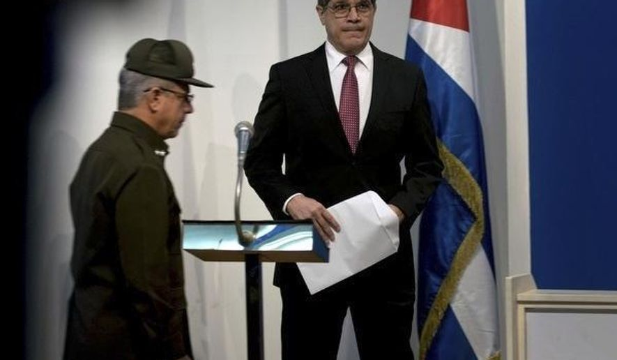 Cuba's Director General of U.S. Affairs Carlos Fernandez de Cossio, center, waits to give a statement to the press as Cuban Interior Ministry investigating officer Lieutenant Colonel Roberto Hernandez Caballero arrives in Havana, Cuba, Thursday, March 14, 2019. Cuban officials made a lengthy presentation on a series of mysterious illnesses suffered by U.S. and Canadian diplomats in Havana, reiterating that no evidence supports allegations that the symptoms resulted from high-tech attacks. (AP Photo/Ramon Espinosa)