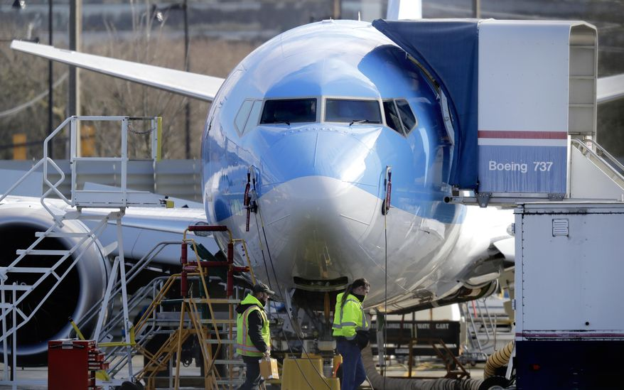 Workers walk past a Boeing 737 MAX 8 airplane being built for TUI Group at Boeing Co.'s Renton Assembly Plant Wednesday, March 13, 2019, in Renton, Wash. (AP Photo/Ted S. Warren)