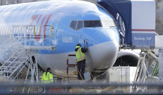 A worker stands on a platform near a Boeing 737 MAX 8 airplane being built for TUI Group at Boeing Co.'s Renton Assembly Plant Wednesday, March 13, 2019, in Renton, Wash. President Donald Trump says the U.S. is issuing an emergency order grounding all Boeing 737 Max 8 and Max 9 aircraft in the wake of a crash of an Ethiopian Airliner. (AP Photo/Ted S. Warren)