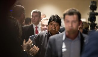 Bolivian President Evo Morales, center, arrives with Greece's Prime Minister Alexis Tsipras, for a press conference in Athens, Thursday, March 14, 2019. Morales is in Greece on a two-day official visit. (AP Photo/Petros Giannakouris)