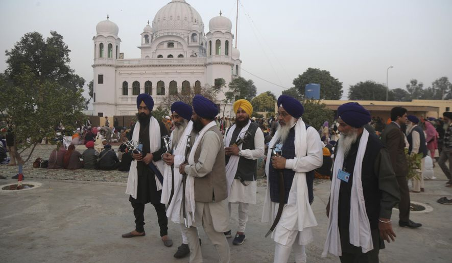 FILE - In this Nov. 28, 2018 file photo, Indian Sikh pilgrims visit  Gurdwara Darbar Sahib, the shrine of their spiritual leader Guru Nanak Dev in Kartarpur, Pakistan.  Officials from India and Pakistan met Thursday, March 14, amid easing tensions to discuss opening a visa-free border crossing to allow pilgrims to easily visit the Sikh shrine just inside Pakistan.(AP Photo/K.M. Chaudary, File)