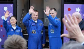U.S. astronauts Christina Hammock Koch, left, Nick Hague, right, and Russian cosmonaut Alexey Ovchinin, members of the main crew to the International Space Station (ISS), pose near a bus prior to the launch of the Soyuz FG rocket at the Russian leased Baikonur cosmodrome, Kazakhstan, Wednesday, March 13, 2019. The new Soyuz mission to the International Space Station (ISS) is scheduled on Thursday, March. 14. (AP Photo/Dmitri Lovetsky)