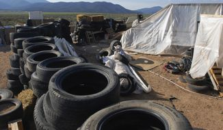 FILE - In this Aug. 10, 2018, file photo, is a makeshift living compound in Amalia, N.M. The five men and women found living in a ramshackle compound in northern New Mexico where a boy was found dead last year have been indicted on federal charges related to terrorism, kidnapping and firearms violations. The U.S. attorney's office in New Mexico announced the superseding indictment Thursday, March 14, 2019. (AP Photo/Morgan Lee, File)