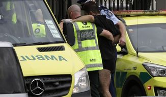Police and ambulance staff help a wounded man from outside a mosque in central Christchurch, New Zealand, Friday, March 15, 2019.  A witness says many people have been killed in a mass shooting at a mosque in the New Zealand city of Christchurch. (AP Photo/Mark Baker)