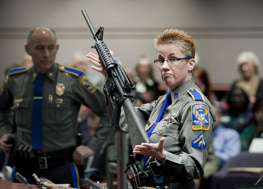 FILE - In this Jan. 28, 2013, file photo, firearms training unit Detective Barbara J. Mattson, of the Connecticut State Police, holds a Bushmaster AR-15 rifle, the same make and model used by Adam Lanza in the 2012 Sandy Hook School shooting, during a hearing at the Legislative Office Building in Hartford, Conn. The Connecticut Supreme Court is expected to rule Thursday, March 14, 2019, whether or not Remington Arms, which manufactured the rifle, can be sued for making the rifle that was used in the massacre. (AP Photo/Jessica Hill, File)