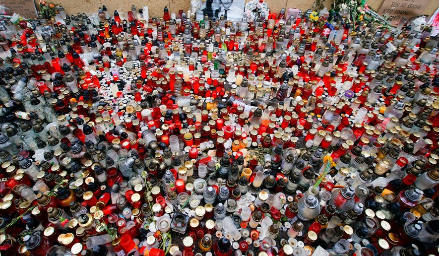 FILE- In this Friday, March 16, 2018 file photo candles are placed in memory of slain journalist Jan Kuciak and his fiancee Martina Kusnirova during a rally in Bratislava, Slovakia. On Thursday, March 14, 2019, Slovakia's police said they have charged a suspect with ordering the slaying of an investigative reporter and his fiancee, a case that brought down the Slovak government. Police didn't immediately name the suspect. Jan Kuciak and Martina Kusnirova were shot dead in their home on Feb. 21 2018. (AP Photo/Darko Vojinovic, File)