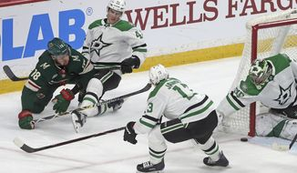 Dallas Stars goalie Ben Bishop, right, stops a shot by Minnesota Wild's Jordan Greenway, left, as Stars' Taylor Fedun, second from left, defends in the first period of an NHL hockey game Thursday, March 14, 2019, in St. Paul, Minn. (AP Photo/Jim Mone)