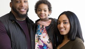 FILE - In this April 12, 2016, file photo, Devon Still and his fiancee, Asha Joyce, pose with their daughter, Leah, then 5, in New York. Leah was diagnosed in 2014 with cancer and became an inspiration to millions as her football-playing father shared details of her brave fight. She was given a prognosis of just over 50 percent to survive stage 4 neuroblastoma. Leah is now a healthy 8-year-old girl in third grade who lives in Houston. Devon Still has become an author, motivational speaker, and an inspiration--especially to strangers suffering like his family did. (AP Photo/Mark Lennihan, File)