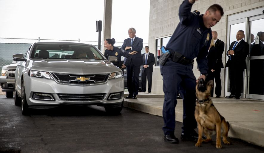 Customs agent Patrick Dowling rewards his dog Balbina after he finds a bag of drugs in a vehicle as Vice President Mike Pence, center, observes Point of Entry training at the U.S. Customs and Border Protection Advanced Training Facility in Harpers Ferry, W.Va., Wednesday, March 13, 2019. (AP Photo/Andrew Harnik)