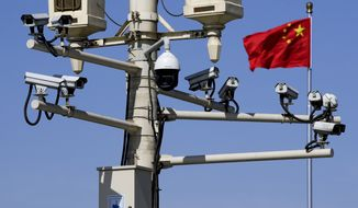 A Chinese national flag flutters near the surveillance cameras mounted on a lamp post in Tiananmen Square in Beijing, Friday, March 15, 2019. Chinese Premier Li Keqiang on Friday denied Beijing tells its companies to spy abroad, refuting U.S. warnings that Chinese technology suppliers might be a security risk. (AP Photo/Andy Wong)
