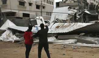 Palestinians inspect the damage of destroyed building belonging to Hamas ministry of prisoners hit by Israeli airstrikes in Gaza City, early Friday, Friday, March 15, 2019. Israeli warplanes attacked militant targets in the southern Gaza Strip early Friday in response to a rare rocket attack on the Israeli city of Tel Aviv, as the sides appeared to be hurtling toward a new round of violence. (AP Photo/Adel Hana)