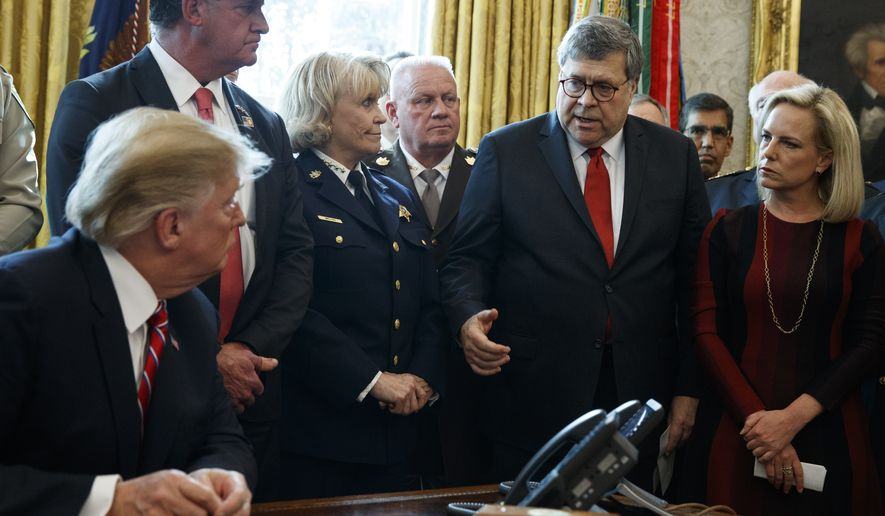 Attorney General William Barr speaks to President Donald Trump before he signs the first veto of his presidency in the Oval Office of the White House, Friday, March 15, 2019, in Washington. Trump issued the first veto, overruling Congress to protect his emergency declaration for border wall funding. (AP Photo/Evan Vucci)