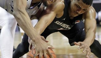 San Diego State's Matt Mitchell, right, and Nevada's Tre'Shawn Thurman reach for a loose ball during the first half of an NCAA college basketball game in the Mountain West Conference men's tournament Friday, March 15, 2019, in Las Vegas. (AP Photo/Isaac Brekken)