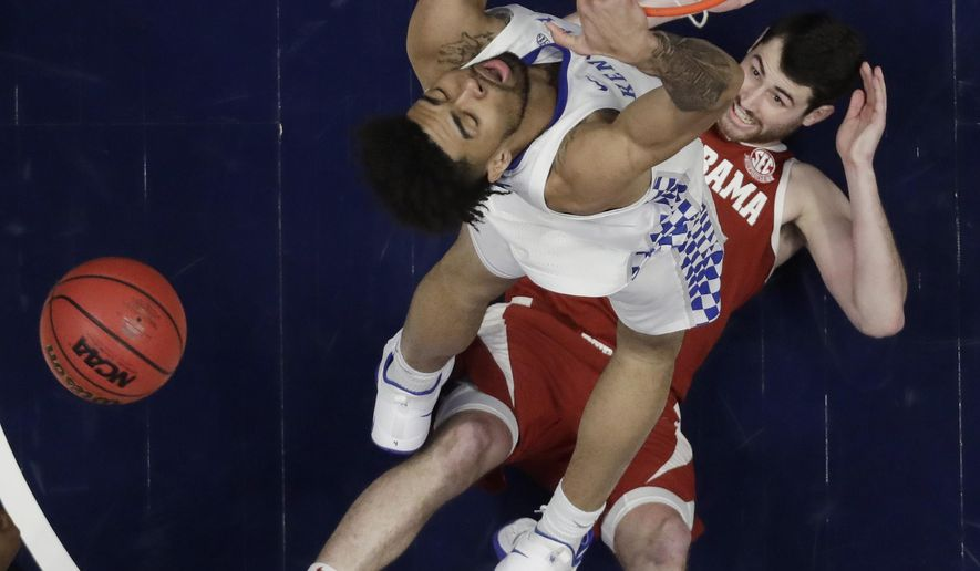 Alabama guard Riley Norris watches from the floor as Kentucky forward Nick Richards dunks the ball above him in the first half of an NCAA college basketball game at the Southeastern Conference tournament Friday, March 15, 2019, in Nashville, Tenn. (AP Photo/Mark Humphrey)