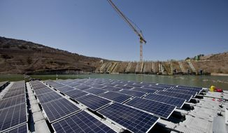 An island of solar panels floats in a pond at the Los Bronces mining plant, about 65 kilometers (approximately 40 miles) from Santiago, Chile, Thursday, March 14, 2019. The island of solar panels could give purpose to mine refuse in Chile by using them to generate clean energy and reduce water evaporation.(AP Photo / Esteban Felix)