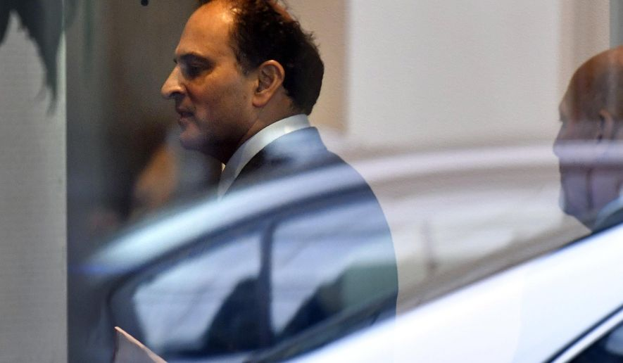 David Sidoo, of Vancouver, Canada, enters an adjacent building with his lawyer following a federal court hearing Friday, March 15, 2019, in Boston. Sidoo faced charges of conspiracy to commit mail and wire fraud as part of a wide-ranging college admissions bribery scandal. (AP Photo/Josh Reynolds)