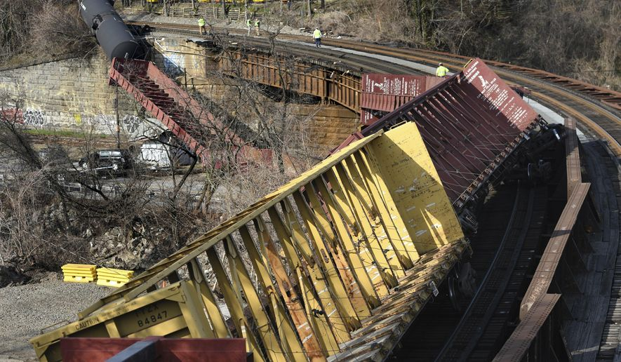 Freight cars hang over Falls Road after a train derailment on a bridge, Friday, March 15, 2019 north of downtown Baltimore. Multiple freight train cars derailed Friday in Baltimore, with at least one empty car tumbling off a bridge, but authorities said no one was injured. (Jerry Jackson/The Baltimore Sun via AP)