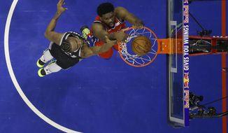 Philadelphia 76ers' Joel Embiid, right, dunks the ball past Sacramento Kings' Harry Giles III during the first half of an NBA basketball game, Friday, March 15, 2019, in Philadelphia. (AP Photo/Matt Slocum)