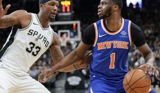 New York Knicks' Emmanuel Mudiay (1) looks to pass as he is defended by San Antonio Spurs' Dante Cunningham during the first half of an NBA basketball game Friday, March 15, 2019, in San Antonio. (AP Photo/Darren Abate)