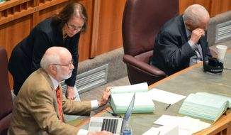 New Mexico Democratic Senate Majority Whip Mimi Stewart, standing, talks to Sen. Gerald Ortiz y Pino, D-Albuquerque, while Sen. John Pinto, D-Gallup, listens to debate on the Senate floor on Friday, March 15, 2019 in Santa Fe, N.M. The Democratic-controlled New Mexico Legislature is racing to pass a number of measures around taxes and minimum wage before the current session ends on Saturday, March 16, 2019. (AP Photo/Russell Contreras)