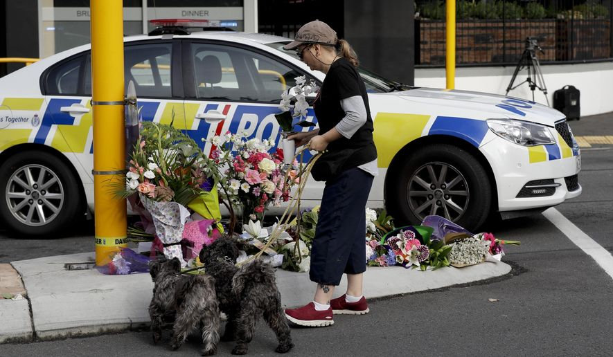 A women places flowers at a makeshift memorial near the Masjid Al Noor mosque in Christchurch, New Zealand, Saturday, March 16, 2019, where one of the mass shootings occurred yesterday. (AP Photo/Mark Baker)
