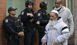 Men leave the Islamic Cultural Center of New York under increased police security following the shooting in New Zealand, Friday, March 15, 2019, in New York. (AP Photo/Mark Lennihan)