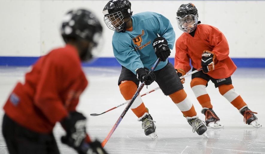 In this Feb. 21, 2019 photo Malakye Johnson takes part in a Snider Hockey practice at the Scanlon Ice Rink in Philadelphia. (AP Photo/Matt Rourke)