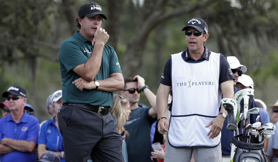 Phil Mickelson, left, listens to his brother and caddie Tim Mickelson as he waits to tee off on the ninth hole during the second round of The Players Championship golf tournament Friday, March 15, 2019, in Ponte Vedra Beach, Fla. (AP Photo/Lynne Sladky)