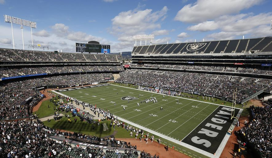 FILE - In this Oct. 28, 2018, file photo, fans watch during the first half of an NFL football game between the Oakland Raiders and the Indianapolis Colts at Oakland Alameda County Coliseum in Oakland, Calif. The Coliseum Authority approved a lease agreement on Friday, March 15, 2019,  to keep the Raiders in Oakland for at least one more season. (AP Photo/D. Ross Cameron, File)
