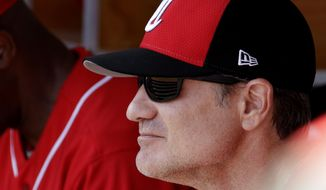 Cincinnati Reds' manager David Bell watches from the dugout during the first inning of a spring training baseball game against the Milwaukee Brewers, Sunday, March 3, 2019, in Phoenix. (AP Photo/Charlie Riedel)