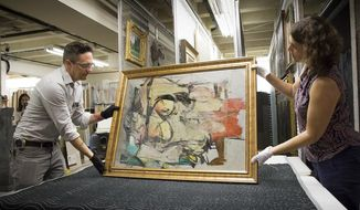 """This August 2017 photo shows """"Woman-Ochre,"""" a painting by Willem de Kooning, being readied for examination by University of Arizona Museum of Art staff Nathan Saxton, left, and Kristen Schmidt in Tucson, Ariz. More than 30 years after it was stolen from the museum, the recovered painting will be on display back where it all began. (Robert Demers/University of Arizona Communications via AP)"""