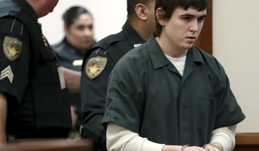 FILE - In this Feb. 25, 2019 file photo Dimitrios Pagourtzis, the Santa Fe High School student accused of killing 10 people in a May 18 shooting at the high school, is escorted by Galveston County Sheriff's Office deputies into the jury assembly room for a change of venue hearing at the Galveston County Courthouse in Galveston, Texas. A state lawmaker is proposing changes to a bill that would leave certain underage offenders eligible for parole after 20 years after hearing opposition from families of victims involved in a Texas high school shooting last May.   (Jennifer Reynolds/The Galveston County Daily News via AP, Pool)
