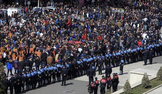 Protesters gather outside the Prime Minister's office during an anti-government rally in Tirana, Albania, Saturday, March 16, 2019. Thousands of supporters of the center-right Democratic Party-led opposition have gathered on Saturday in front of Socialist Party's Prime Minister Edi Rama to demand his resignation, a transitory Cabinet without him that will prepare fresh elections. (AP Photo/ Hektor Pustina)