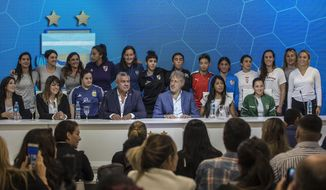 Accompanied by soccer players, Claudio Tapia, president of Argentina's Soccer Federation, bottom center, and General Secretary of the Argentina's Footballers' Union (FAA) Sergio Marchi, bottom, second from right, pose for pictures during a press conference to announce the early implementation of a plan to professionalize women's soccer in Buenos Aires, Argentina, Saturday, March 16, 2019. Almost 90 years after men's soccer turned professional in Argentina, the women's game is still being played by amateur athletes who get little to no money for their work on the field. (AP Photo/Daniel Jayo)