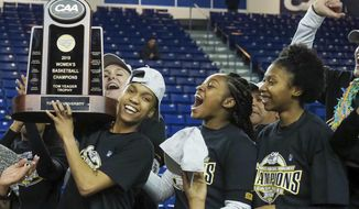 Towson forward Nukiya Mayo (1) holds the trophy as they celebrate their 53-49 win over Drexel in an NCAA college basketball game in the championship of the Colonial Athletic Association tournament, Saturday, March 16, 2019, in Newark, Del. (AP Photo/Suchat Pederson)
