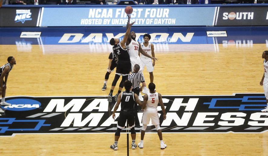 FILE - In this March 13, 2018, file photo, Radford's Randy Phillips (32) and LIU Brooklyn's Julius van Sauers (2) tip off during the first half of a First Four game of the NCAA men's college basketball tournament, in Dayton, Ohio. Dayton stages the four play-in games over two nights, assuring the city and the private University of Dayton a nice slice of the NCAA Tournament pie every March. The city will host the event at least through 2022 after beating out Detroit and Evansville, Indiana, for the current four-year contract. (AP Photo/John Minchillo, File)